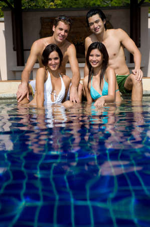 wealthy lifestyle: Four young friends in the pool on vacation Stock Photo