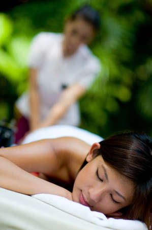 thai orchid: A young woman having massage outside in tropical garden Stock Photo