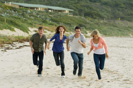 20s adult: Four friends running along a sandy beach in autumn
