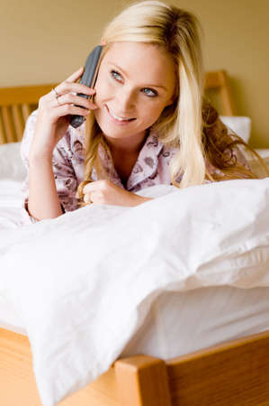 A young attractive woman talking on phone in bed photo