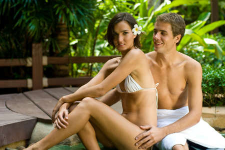 A young attractive couple lying by a jacuzzi in tropical setting photo