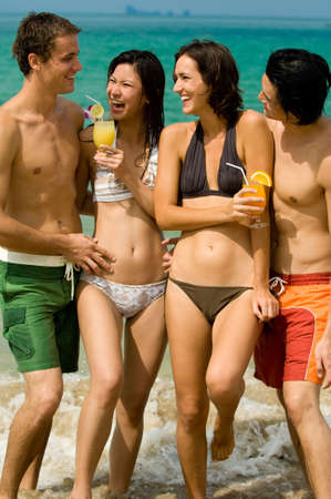 Four friends on the beach with drinks photo