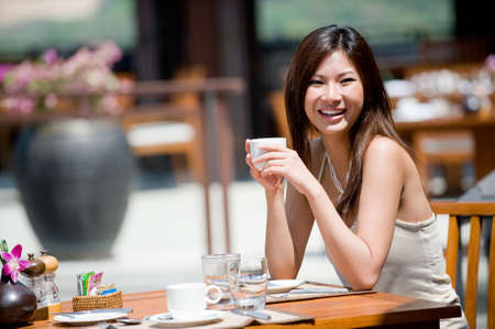 outdoor cafe: A young woman sitting alone at breakfast table at resort Stock Photo