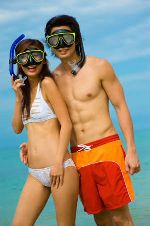 A young couple with snorkelling gear on a tropical beach Stock Photo - 3564816