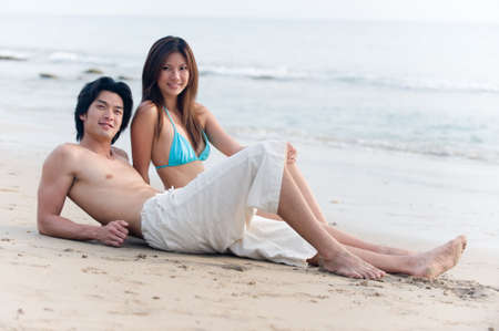 A young couple sitting on the beach together photo