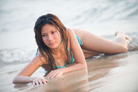 A young attractive asian woman lying on the beach near the sea photo