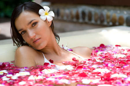 A young woman in a bath full of flowers photo