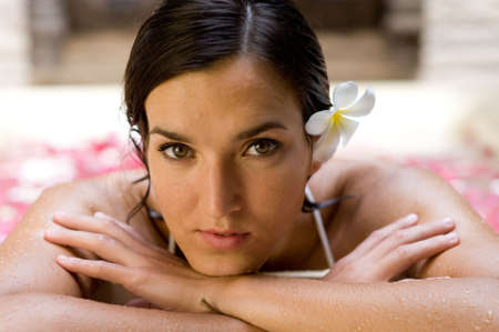 A beautiful young woman in a bath of flowers at a spa photo