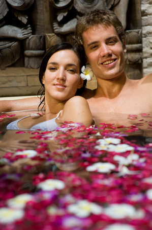 pamper: A young couple together in a bath with petals and flowers at a tropical spa Stock Photo