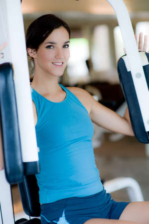 woman chest: A young woman working out on a machine in a gym