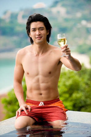 A young Chinese man sitting on edge of pool with glass of wine photo
