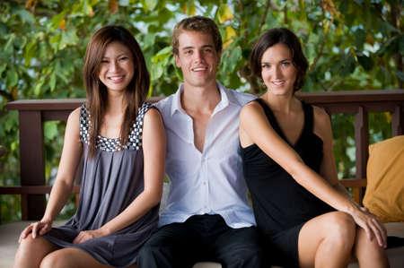 trio: Tres atractivas j�venes adultos sentados juntos en la ropa inteligente