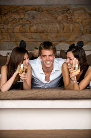 Three attractive young adults lying together in smart clothing photo
