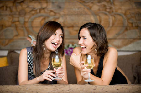 Two young attractive women with wine lying on bed photo