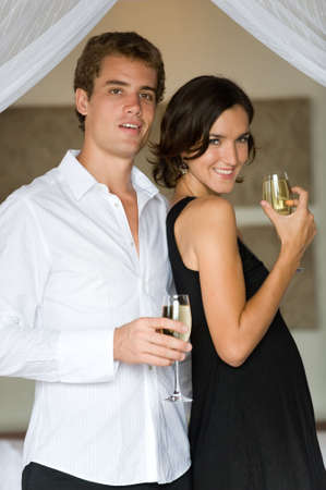 A young couple on honeymoon standing in bedroom with champagne photo