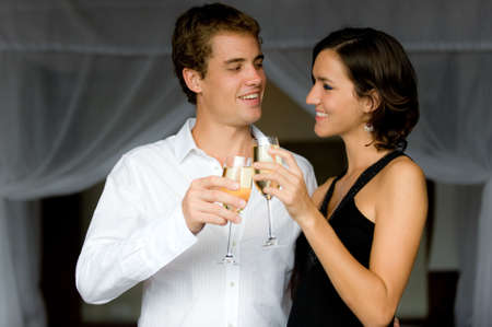 An attractive couple in bedroom with champagne photo