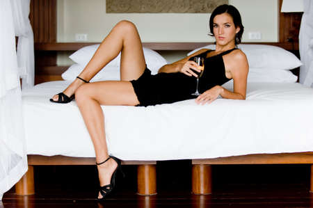 A young woman drinking champagne on the bed Stock Photo