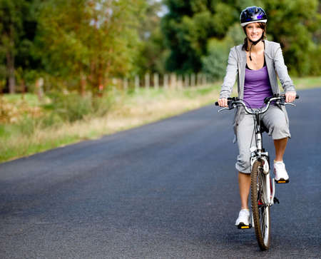 A young attractive woman cycling on a country road Stock Photo