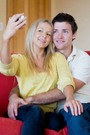 A young couple taking their photograph at home on the sofa Stock Photo - 3582268