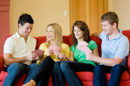 Four friends sitting at home on the sofa playing cards photo