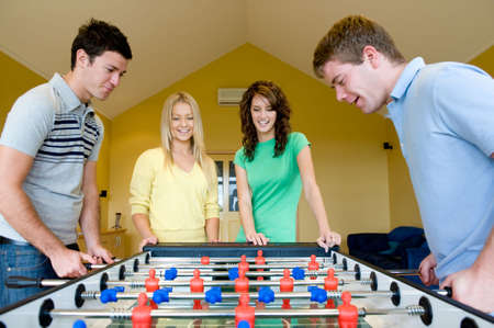 opponents: Four friends playing table football at home