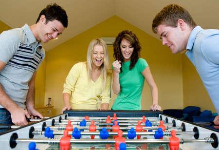 Quatre amis à jouer au baby-foot à la maison