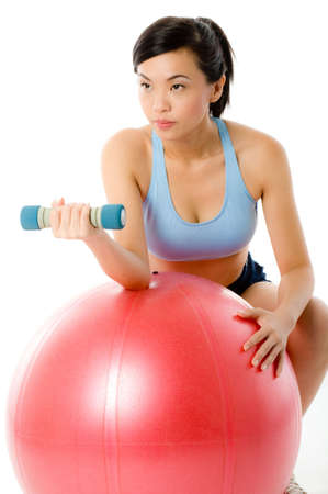 A young attractive Asian woman in sportswear working out with dumbbells