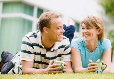 pareja hogar: Una joven pareja se extiende fuera en el jard�n enfrente de casa Foto de archivo