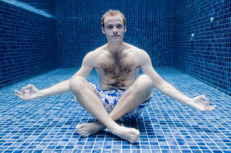 swimming trunks: A young man looking relaxed underwater in a swimming pool Stock Photo