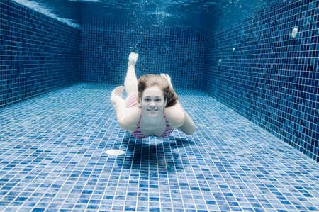 underwater woman: An underwater shot of a woman in a swimming pool Stock Photo