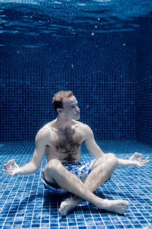 underwater pool: An underwater shot of a man in a swimming pool trying to relax Stock Photo