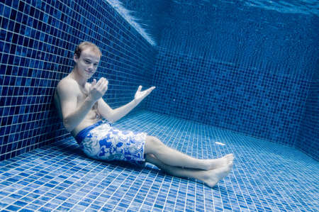 An underwater shot of a man in a swimming pool trying to relax photo