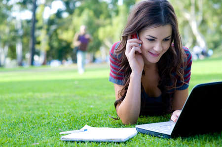 A young attractive woman studying  outside