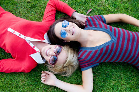 Two young attractive women lying together on the grass photo