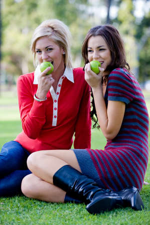 Two young attractive women sitting outside on the lawn with apples photo