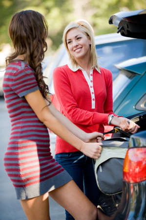 Two female students putting large bag into the car photo