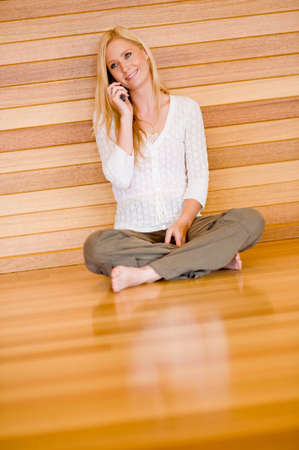 A young attractive woman sitting on floor at home with laptop and phone photo
