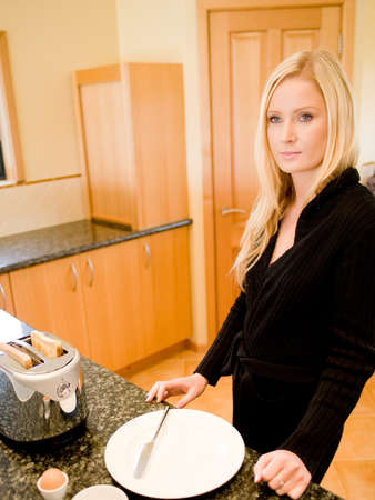 A young attractive woman making breakfast in the kitchen photo