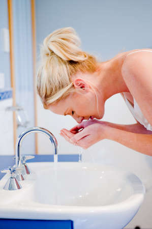 washing face: A young attractive woman washing her face in the bathroom
