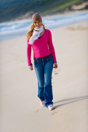 adult footprint: A young attractive woman walking along a sandy beach in autumn
