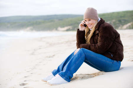 wooly: A young attractive woman outside on a beach in winter wear using mobile phone