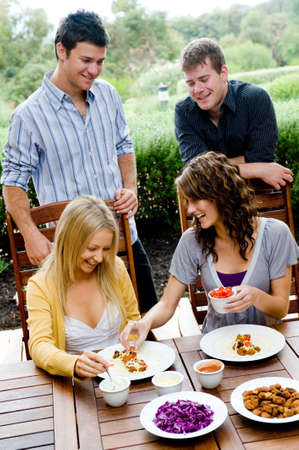 Four young adults having dinner together photo