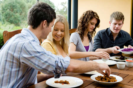 Four young adults having dinner together Stock Photo