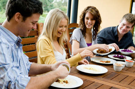 dinner party people: Four young adults having dinner together Stock Photo