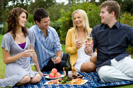 Four young adults celebrating with champagne and picnic outside in the garden