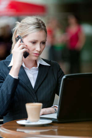 A young attractive businesswoman sitting at a cafe with a laptop and phone Stock Photo - 4059659