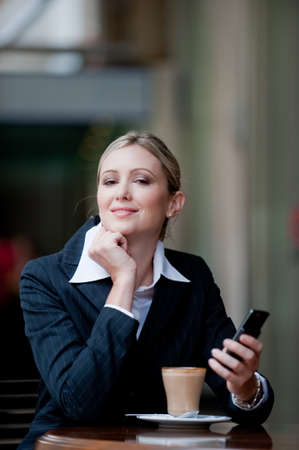 A young attractive businesswoman sitting at a cafe with her mobile phone Stock Photo - 4059655