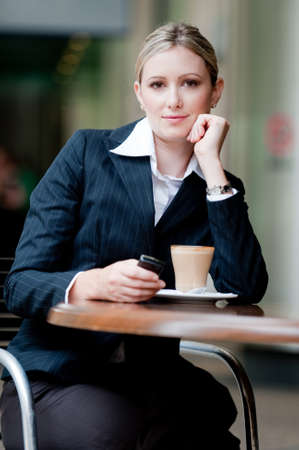 A young attractive businesswoman sitting at a cafe with her mobile phone Stock Photo - 4059648