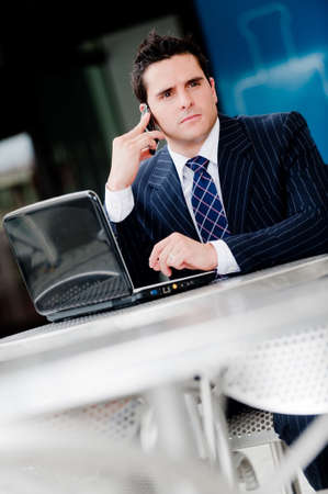 A young professional sitting in outdoor cafe with laptop computer and mobile phone Stock Photo - 4059647