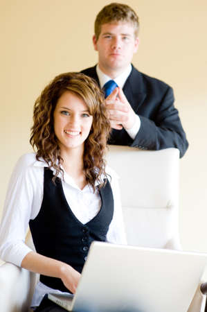 A young businesswoman sitting on leather chair in office with a colleague standing behind photo